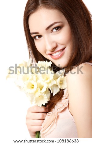 beautiful teen girl smiling and with flower narcissus and looking at camera. isolated on white