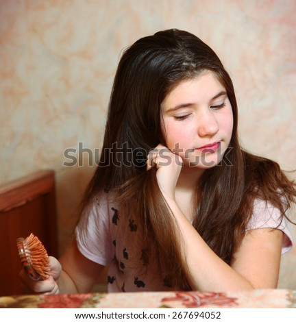 beautiful teen girl try to comb her long dark thick hair - stock photo