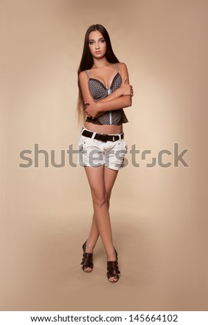 Beautiful teen girl wearing in white shorts and tank top posing on beige background