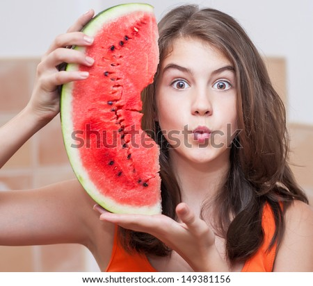 Beautiful teen girl with slice of fresh watermelon .Young girl eating watermelon.Portrait of teenage girl in red t-shirt and long hair holding watermelon slice in the chicken