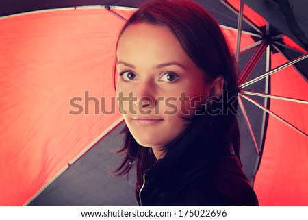 Beautiful teen woman dressed in black under red and black umbrella isolated on white background - stock photo