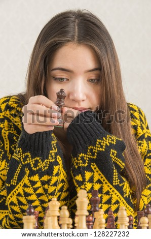 Beautiful teenage girl concentrated and focused on a game of chess - stock photo