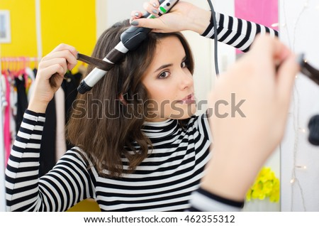 Beautiful teenage girl curling long hair with curler in front of mirror in her room.