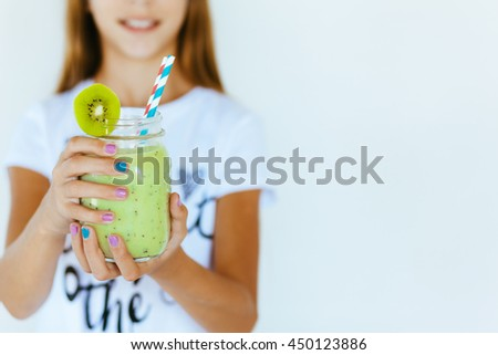Beautiful teenage girl drinking smoothie shake against white wall, focus on hands and jar