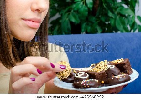 Beautiful teenage girl eating chocolate cookies at home while sitting on couch. - stock photo