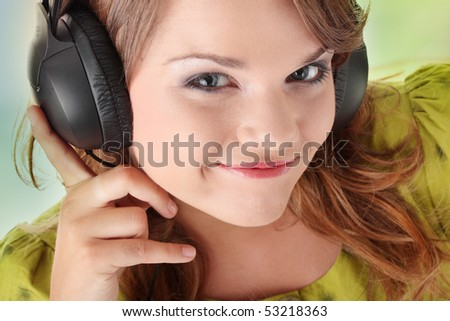Beautiful teenage girl in a green dress listening to music with big headphones