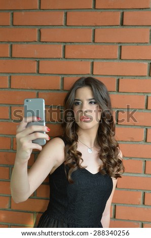 Beautiful teenage girl in black dress taking selfie by cell phone against brick wall background - stock photo