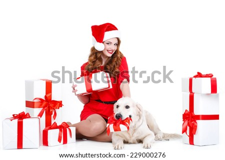 beautiful teenage girl in pajamas lying with dog labrador retriever in santa hat isolated on white background