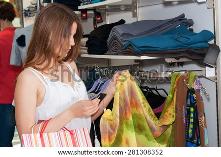 Beautiful teenage girl looking scarf in a boutique - stock photo