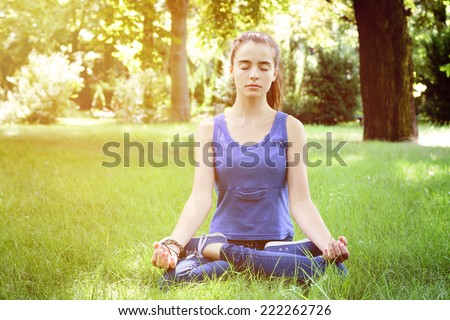 beautiful teenage girl meditates in nature - stock photo