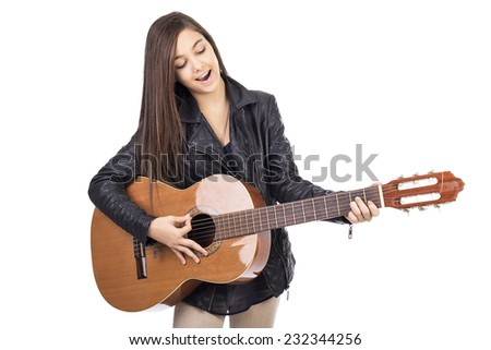 Beautiful teenage girl playing guitar and singing  isolated on white background
