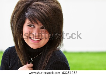 Beautiful teenage girl smiling outside in a black sweater - stock photo