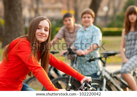 Beautiful teenage girl spending time with her friends riding bicycles. - stock photo