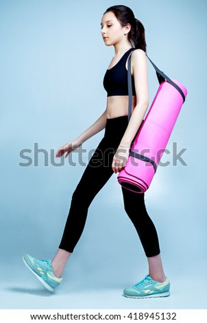 beautiful teenage girl wearing sports clothes going with a yoga mat  - stock photo
