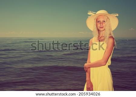 Beautiful teenage girl wearing yellow dress and hat next to the sea. - stock photo