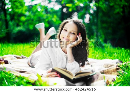 beautiful teenage girl with a book in the park