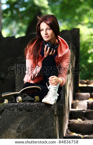 Beautiful teenage girl with headphones and skateboard in the park