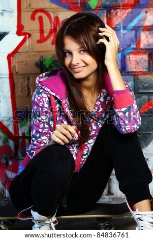 Beautiful teenage girl with headphones sitting on skateboard against a brick wall