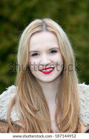 Beautiful teenage girl with long blond hair wearing bright red lipstick looking at the camera with a a lovely smile