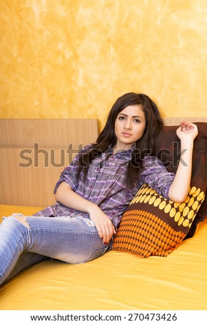 Beautiful teenage girl with shirt and jeans resting on the bed in her room - stock photo