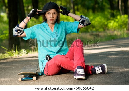 Beautiful teenage girl with skateboard in the green park - stock photo