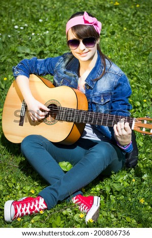 Beautiful teenage girl with the guitar, outdoors