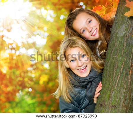 Beautiful Teenage Girls Having Fun in Autumn Park .Outdoor - stock photo