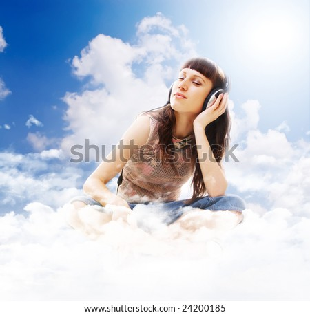 beautiful teenage listening music with pleasure on the clouds - stock photo
