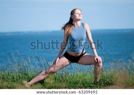 Beautiful teenage sport woman   doing stretching exercise over blue sea landscape. Yoga - stock photo