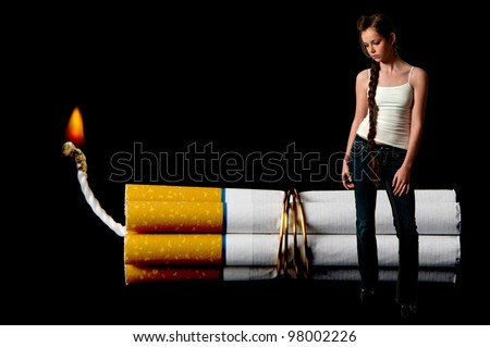 Beautiful teenage woman standing beside several cigarettes bound together like sticks of dynamite - stock photo