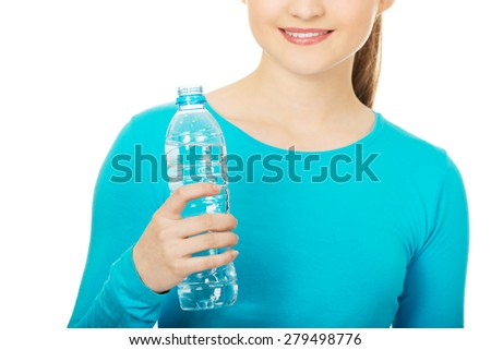 Beautiful teenage woman with bottle of mineral water. - stock photo