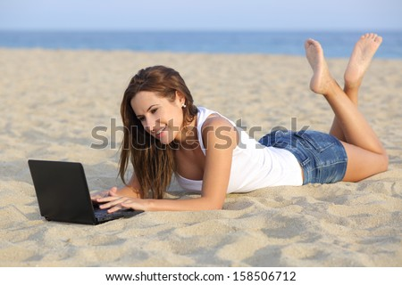 Beautiful teenager girl browsing her netbook computer lying on the sand of the beach with the horizon in the background - stock photo