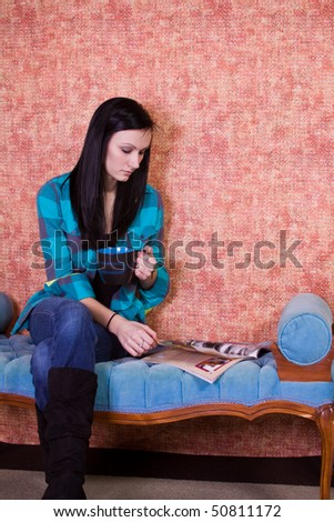 Beautiful  Teenager Girl Drinking Coffee at Home while Reading a Magazine - stock photo