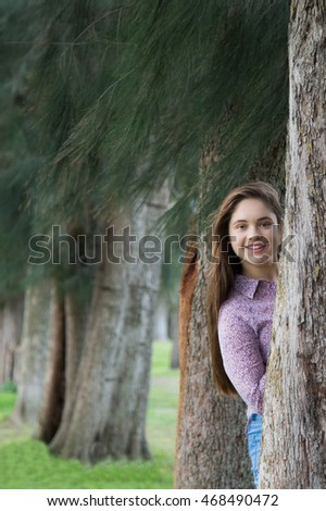 beautiful teenager girl is hiding behind the tree