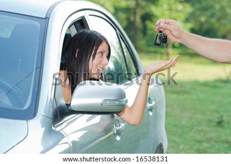 Beautiful teenager receiving car keys - stock photo