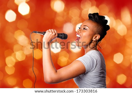 Beautiful teenager woman singing karaoke concert artist holding microphone, on red orange blurred lights background. - stock photo