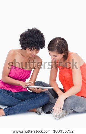 Beautiful teenagers attentively looking at a tablet PC against a white background - stock photo