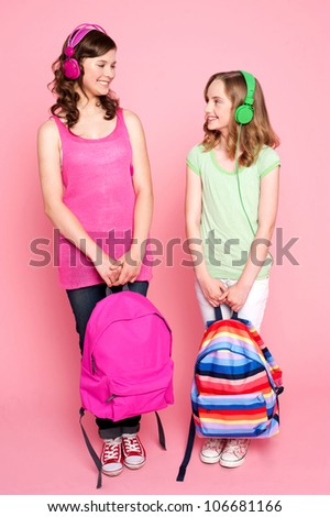 Beautiful teenagers standing with bag in hand and listening to music through headphones - stock photo