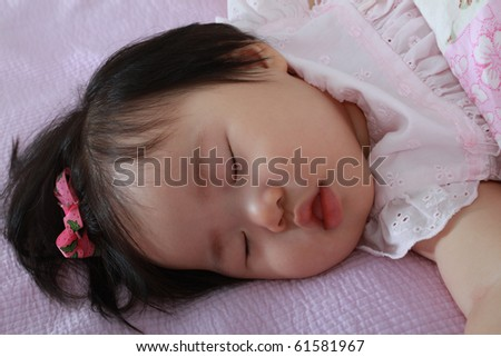 Beautiful Ten Month Old Asian Baby Infant Girl with hairbow sleeping soundly