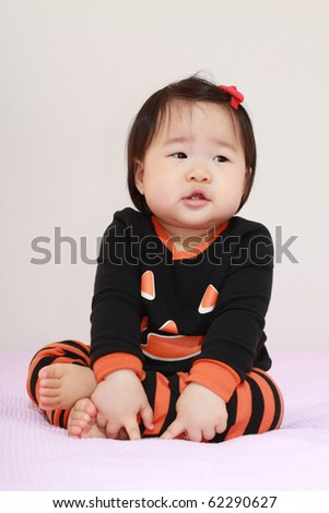 Beautiful ten month old baby asian infant girl in jack o lantern pajamas waiting anxiously for halloween - stock photo