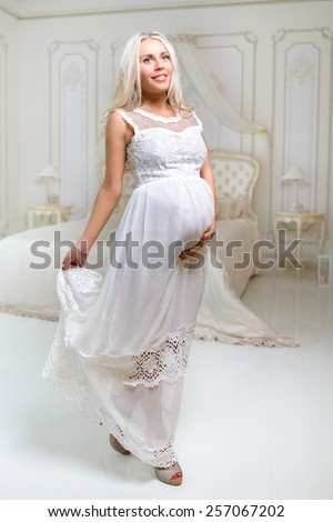 beautiful tender delicate pregnant blond woman in white dress touching her belly in white antique bedroom  - stock photo