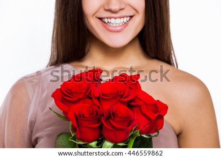 Beautiful tenderness. Portrait of an attractive young woman smiles to camera and holding a bouquet of roses while standing on isolated background - stock photo