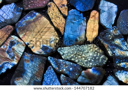 Beautiful texture of natural wet colorful labradorite gem stones. - stock photo
