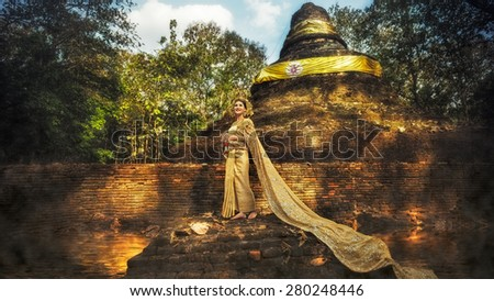 Beautiful Thai lady in Thai traditional drama dress, posing in the ancient remains, greenery in the background, model is Thai Ethnicity. - stock photo