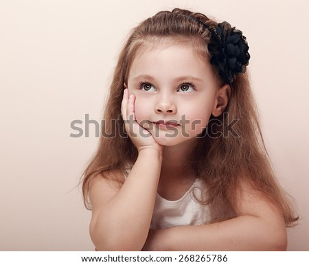 Beautiful thinking kid girl with dreaming eyes. Closeup portrait - stock photo