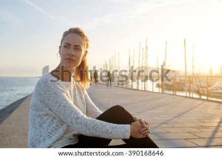 Beautiful thoughtful female tourist enjoys good summer evening and recreation time while sits on pier near sea, cute hipster girl dreams about something and relaxes in the fresh air in her weekend - stock photo