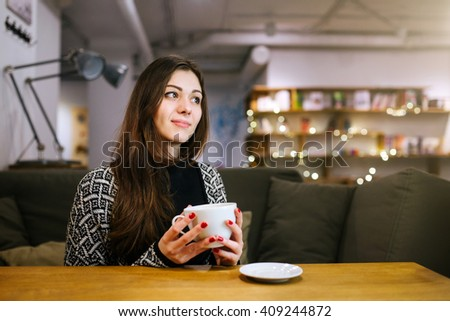 Beautiful thoughtful girl dreaming and drinking coffee. Charming brunette waiting for meeting with friends and drinking tea in a cafe on the background of Christmas lights. - stock photo