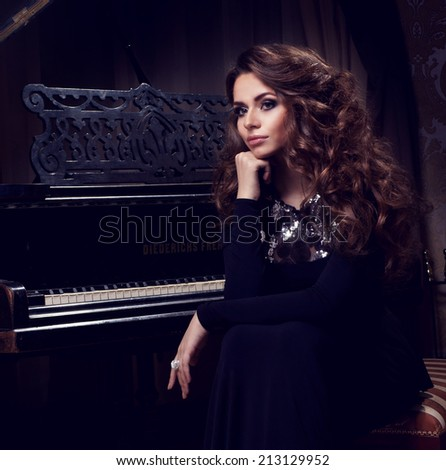 Beautiful thoughtful girl sitting near piano. Fashion studio portrait - stock photo