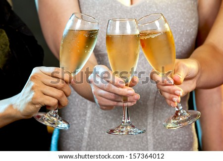 beautiful three women holding glasses with champagne - stock photo