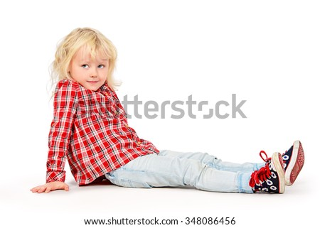 Beautiful three year old girl with curly blonde hair sitting on a floor and smiling. Happy childhood. Kid's beauty, fashion. Isolated over white. - stock photo